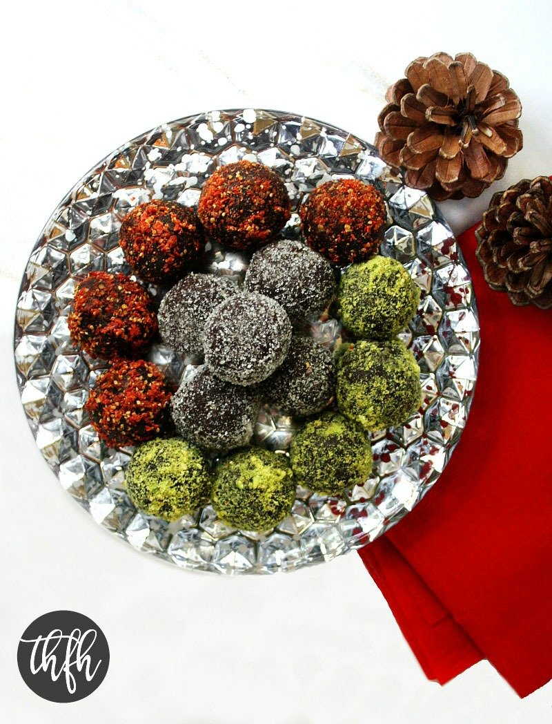 Gluten-Free Vegan Walnut and Cacao No-Cook Holiday Truffles stacked on a silver plate surrounded by Christmas decorations