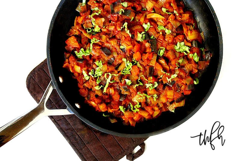 Overhead horizontal image of Vegan Eggplant Onion and Tomato Stew in a black skillet on a white surface