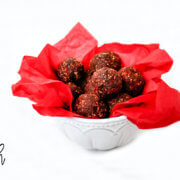 A decorative white bowl lined with red paper filled with chocolate truffles on a solid white background