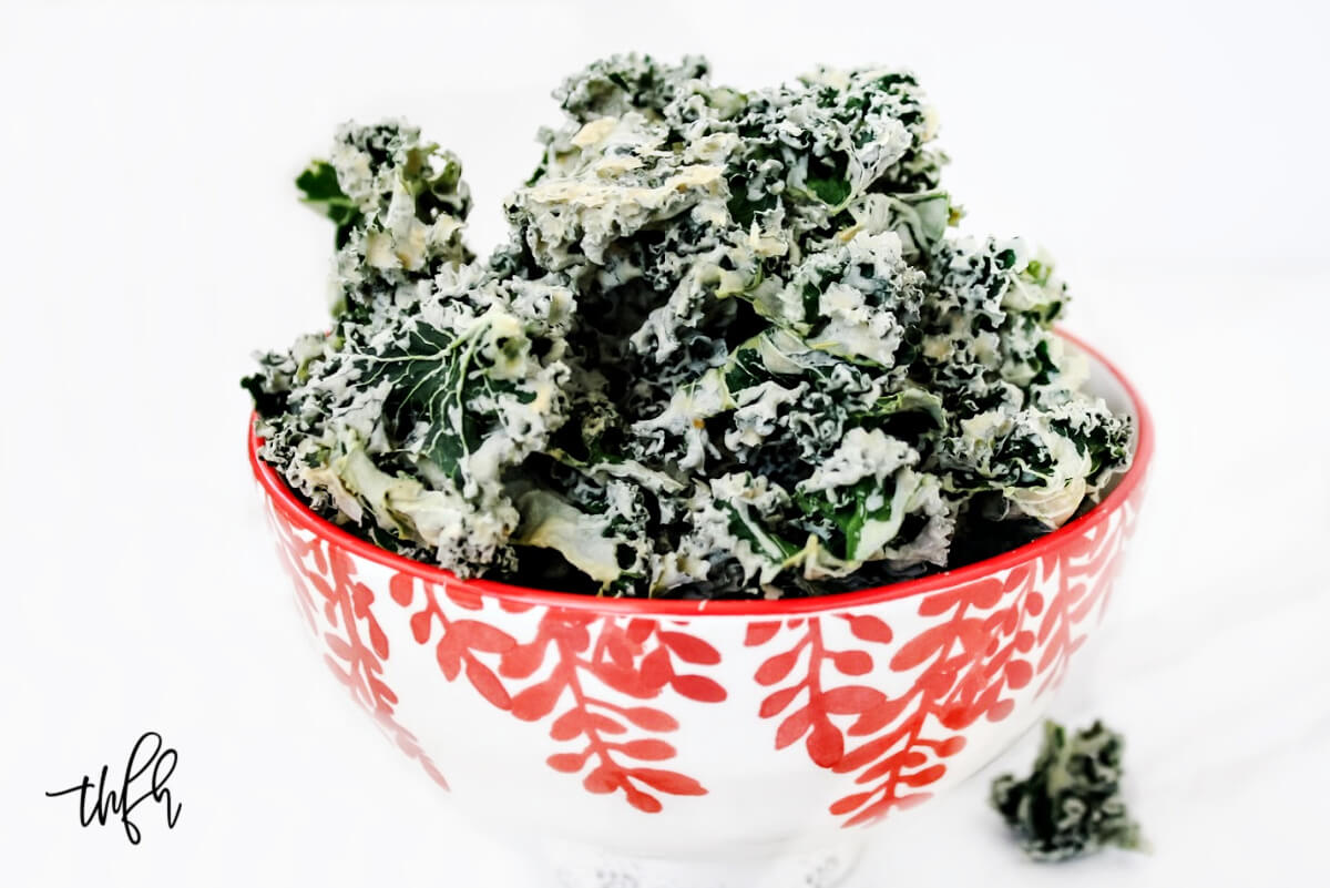 Horizontal image of a decorative red and white bowl filled with habanero kale chips on a solid white background