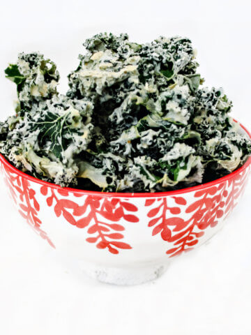Square image of a decorative red and white bowl filled with habanero kale chips on a solid white background