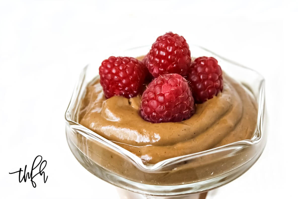 Close-up image of a glass bowl filled with chocolate pudding with four fresh raspberries on top