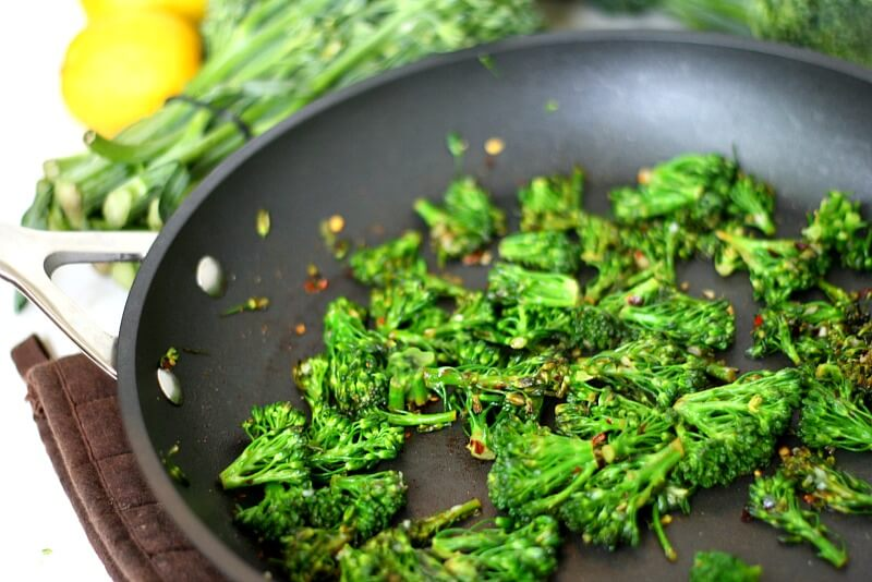 Close-up image of a skillet with Gluten-Free Vegan Spicy Sauteed Broccolini with lemons in the background