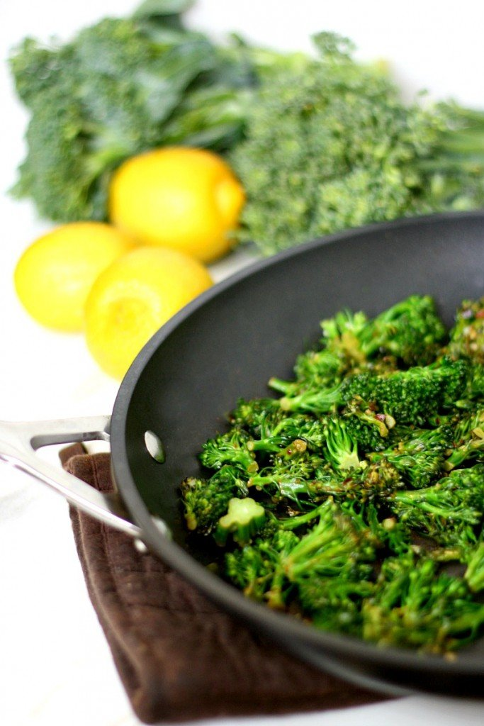 Vertical image of a black non-toxic skillet filled with Gluten-Free Vegan Spicy Lemon Sauteed Broccolini with lemons in the background