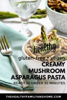 Vertical image of a white bowl of The BEST Gluten-Free Vegan Creamy Mushroom Asparagus Pasta on a wooden surface with text overlay