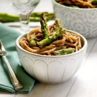Horizontal image of The BEST Gluten-Free Vegan Creamy Mushroom Asparagus Pasta in a white bowl on a wooden surface