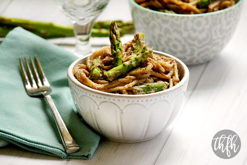 White bowl of The BEST Gluten-Free Vegan Creamy Mushroom Asparagus Pasta on a white wooden surface