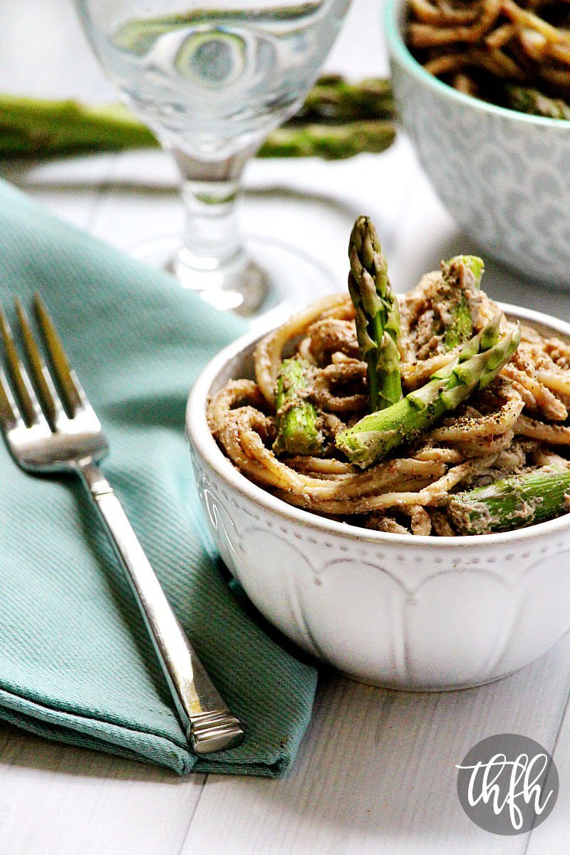Vertical image of a white bowl of The BEST Gluten-Free Vegan Creamy Mushroom Asparagus Pasta on a white wooden surface