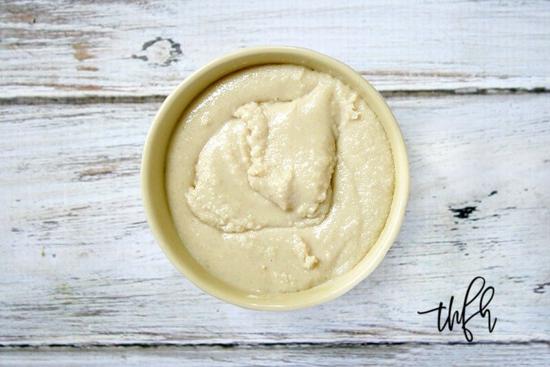 Horizontal image of a cream bowl filled with The BEST Homemade Tahini on a weathered wood background