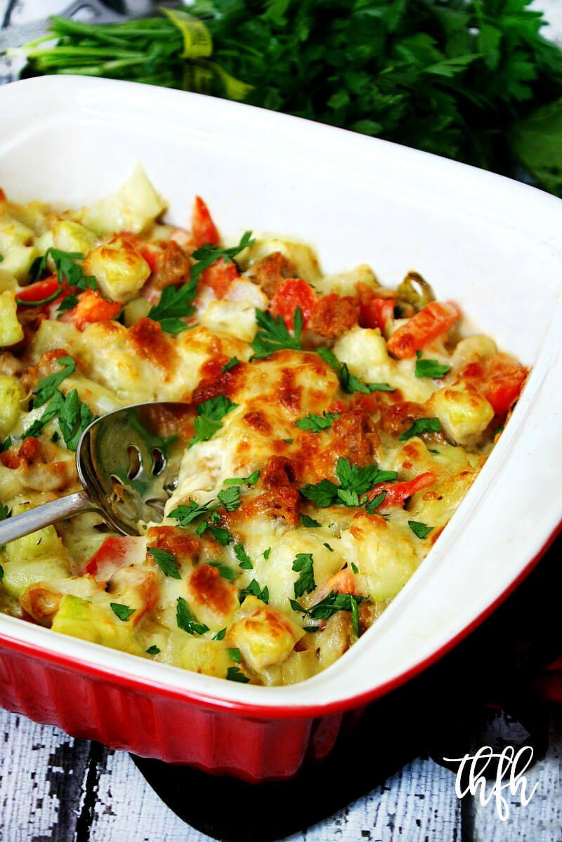 A red casserole dish filled with Spicy Vegan Italian Cucuzza Squash Casserole Bake on a white weathered wooden surface