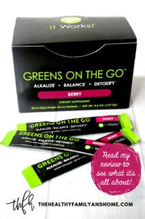 "A box of ""Greens On The Go"" Berry by It Works! on a white wooden surface with text overlay"