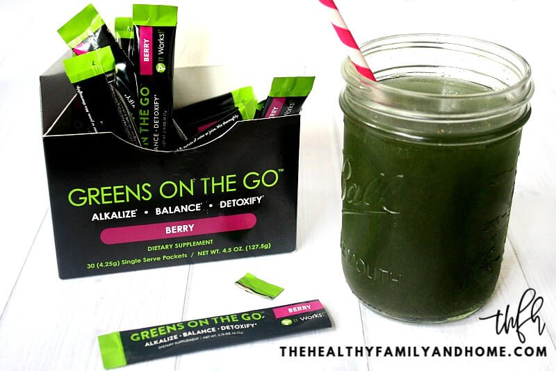"An opened box of ""Greens On The Go"" Berry by It Works! next to a glass and straw on a white wooden background"