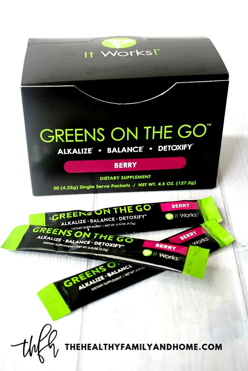 "A box of ""Greens On The Go"" Berry by It Works! on a white wooden surface"