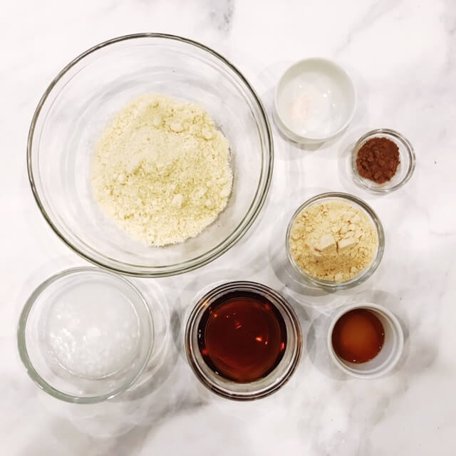 Overhead image of glass bowls holding the ingredients needed to make Gluten-Free Vegan Chocolate Frosted Pumpkin Spice Cookies on a white marbled surface