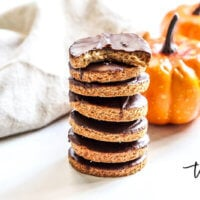 A stack of Gluten-Free Vegan Chocolate Frosted Pumpkin Spice Cookies on a white surface with small pumpkins and a cream cloth napkin in the background
