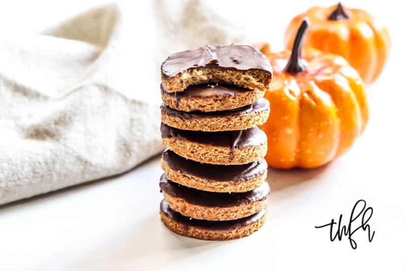 A stack of Gluten-Free Vegan Chocolate Covered Pumpkin Spice Cookies on a white surface with small pumpkins and a cream cloth napkin in the background