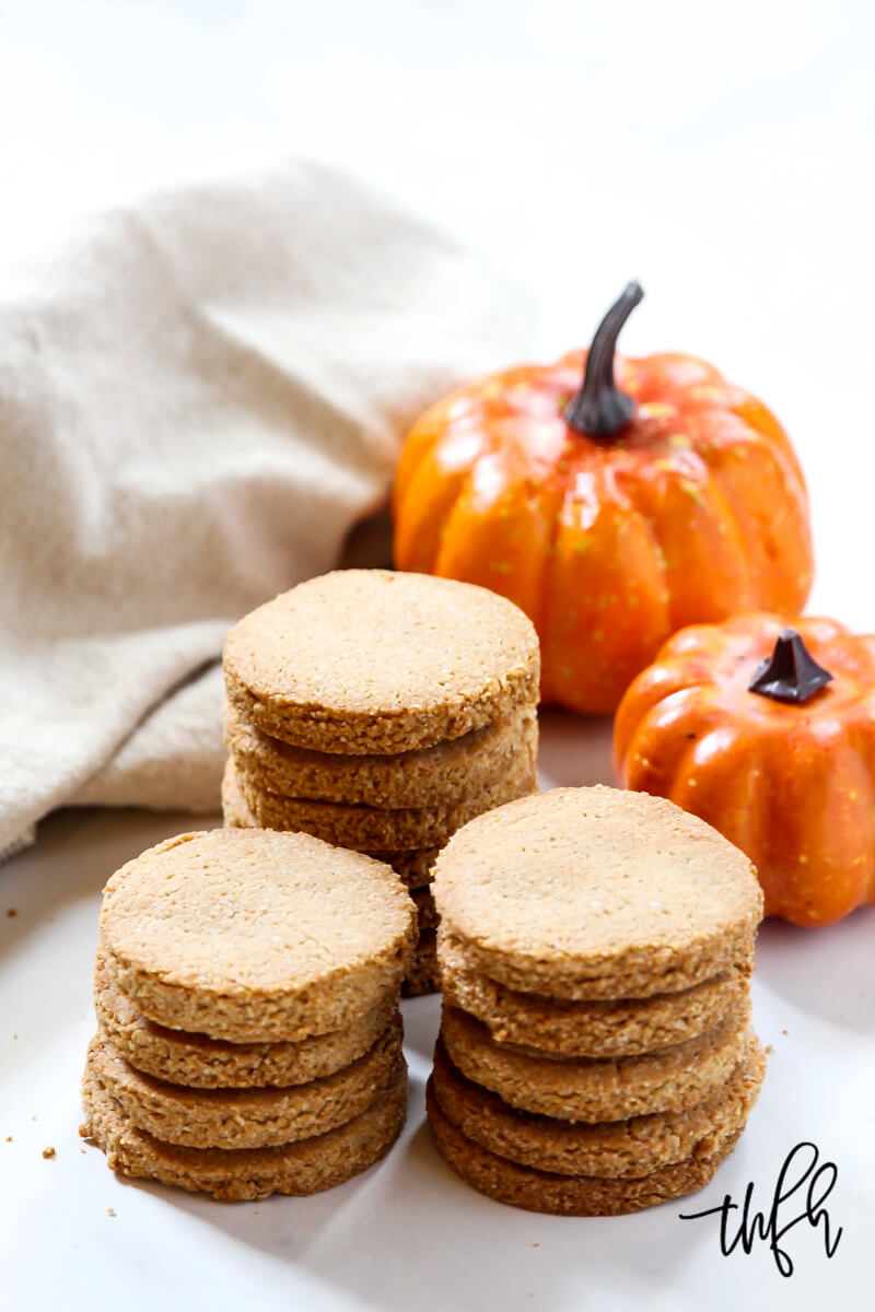 Three stacks of unfrosted Gluten-Free Vegan Chocolate Frosted Pumpkin Spice Cookies with small pumpkins in the background
