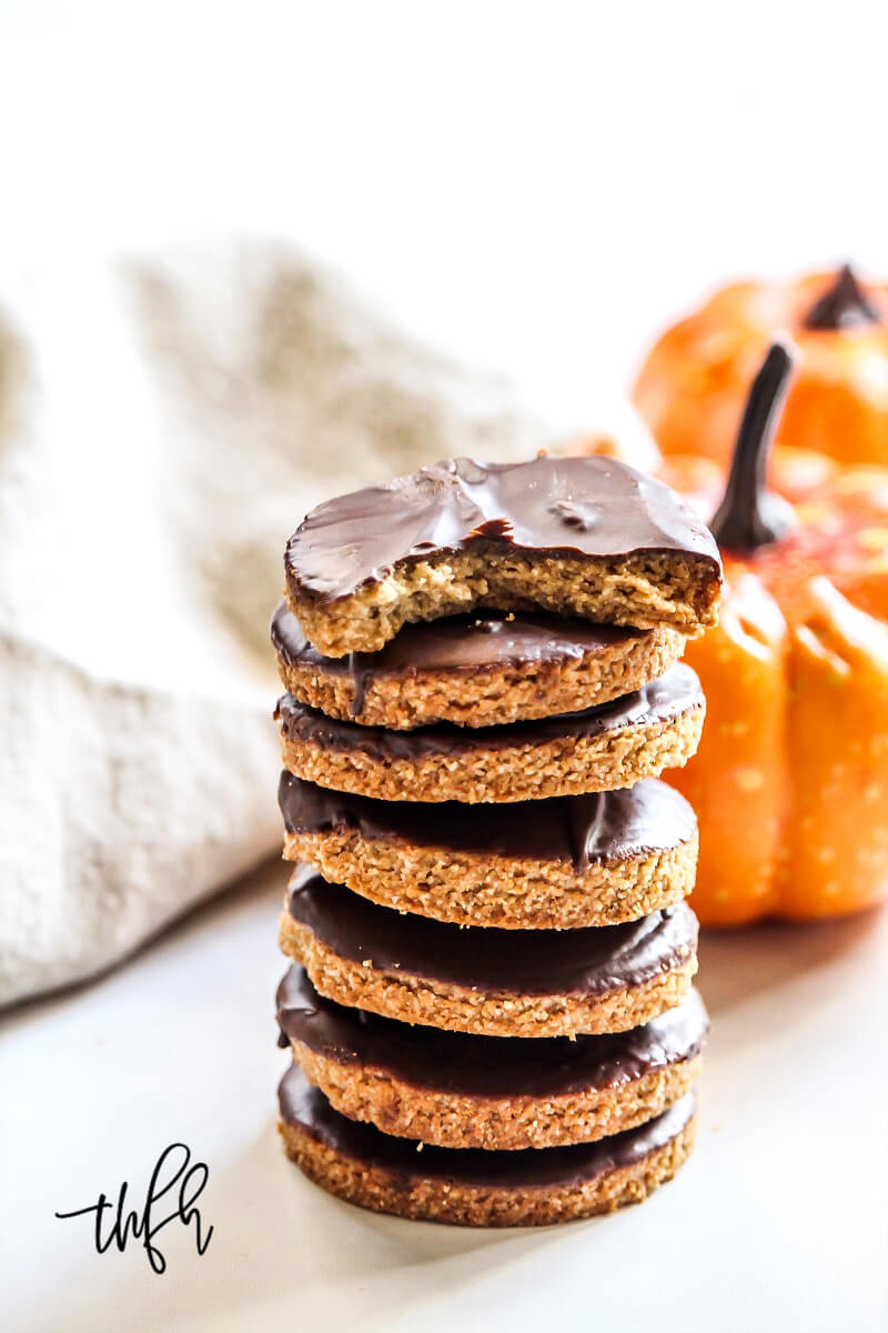 A stack of Gluten-Free Vegan Chocolate Frosted Pumpkin Spice Cookies with two small pumpkins and a cloth napkin in the background