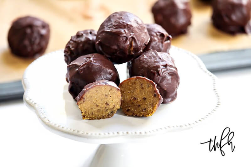 Horizontal image of a grey platter stacked with The BEST Vegan No-Bake Chocolate Covered Pumpkin Truffles with scattered truffles in the background
