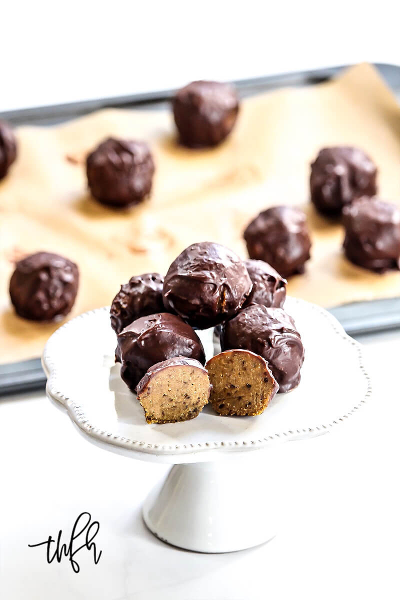 A stack of The BEST Vegan No-Bake Chocolate Covered Pumpkin Truffles on a small platter with more on a cookie sheet in the background
