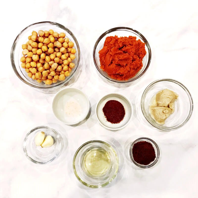 Overhead image of ingredients needed to make Gluten-Free Vegan Smoky Chipotle Pumpkin Hummus in small glass bowls on a white marbled surface