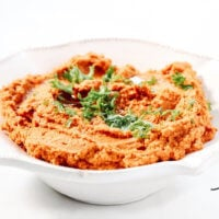 A decorative white bowl filled with Gluten-Free Vegan Smoky Chipotle Pumpkin Hummus centered in the image on a solid white background