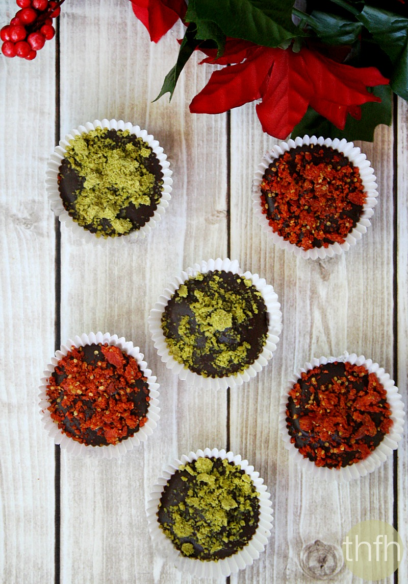 Overhead view of Gluten-Free Vegan No-Cook Dark Chocolate Cups with Pistachios and Goji Berries on a white wooden surface with Christmas follage in the background