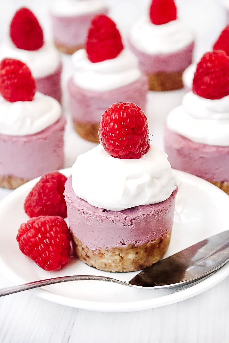 Vertical image of a Gluten-Free Vegan No-Bake Raspberry Mini Cheesecake on a white saucer with silver spoon