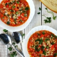 Vertical image of Vegan Stuffed Pepper Soup in two white bowls next to two spoons on a faded wooden surface with a loaf of bread in the background