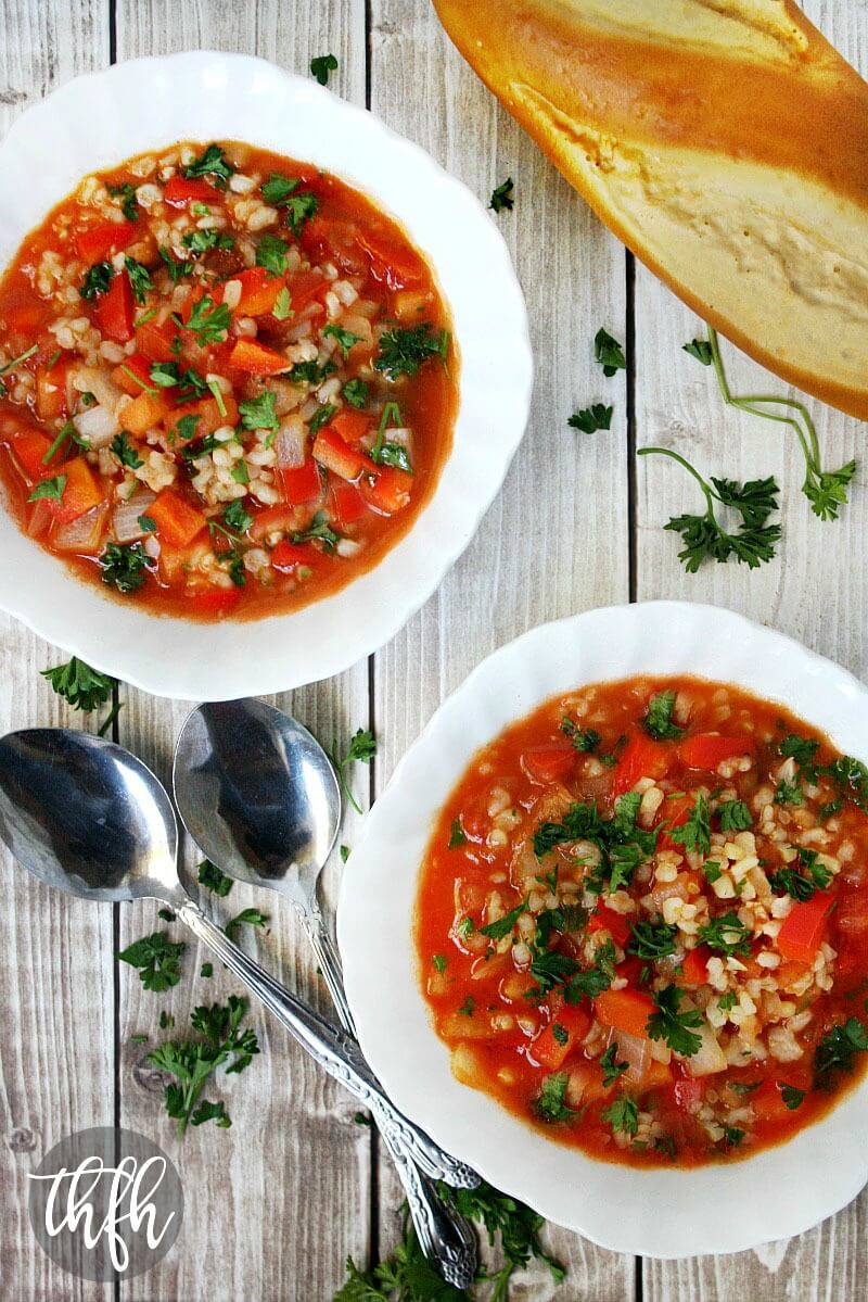 Vertical image of The BEST Vegan Stuffed Pepper Soup in two white bowls next to two spoons on a faded wooden surface and a loaf of bread in the background