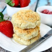 Stack of three Gluten-Free Vegan Biscuits on a white saucer surrounded by strawberries on a wooden surface