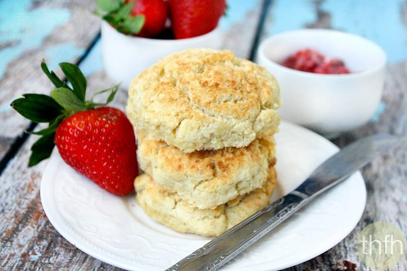 A stack of three Gluten-Free Vegan Biscuits on a white saucer surrounded by strawberries on a weathered wooden surface