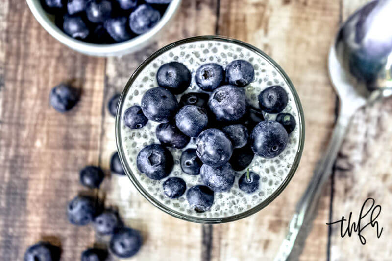 Overhead image of the rim of a glass with Vanilla Bean and Blueberry Chia Seed Pudding on the inside with spilled blueberries on the side on top of a weathered wooden surface