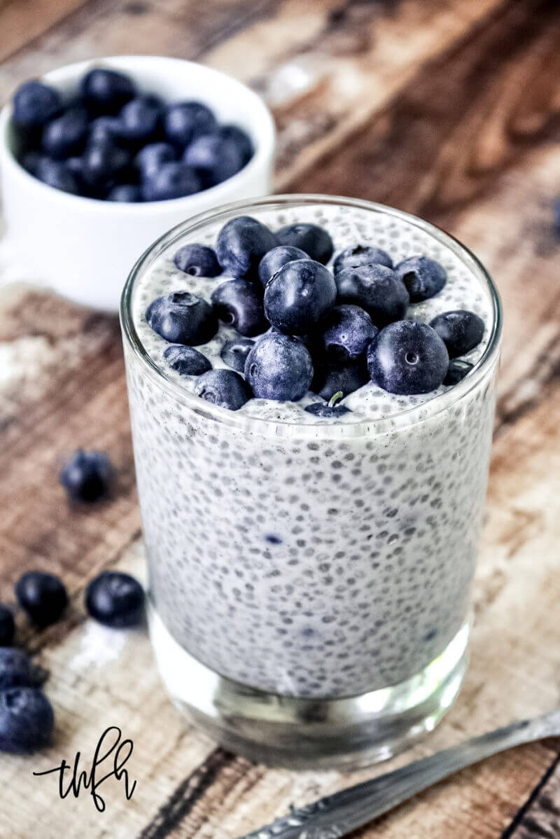 Vertical image of a glass filled with Vanilla Bean and Blueberry Chia Seed Pudding with fresh blueberries on top on a weathered wooden surface