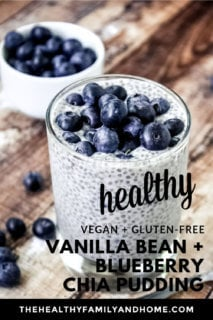 Vertical image of a glass full of Vanilla Bean and Blueberry Chia Seed Pudding on a weathered wooden surface with a small bowl of blueberries in the background with text overlay