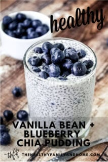 A glass of Vanilla Bean and Blueberry Chia Seed Pudding garnished with fresh blueberries on top of a weathered wooden surface with text overlay