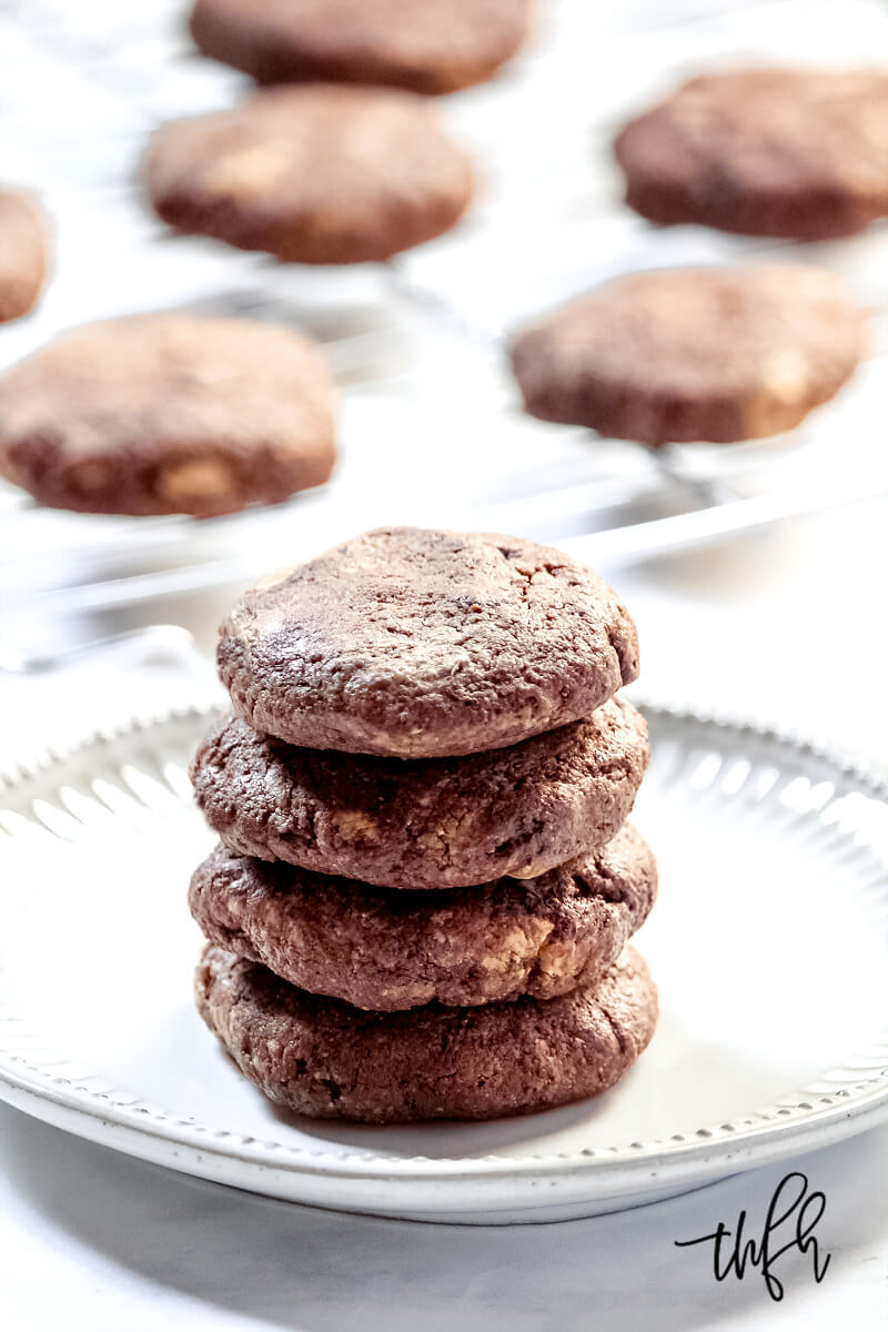 Stack of four Gluten-Free Vegan Flourless Chocolate Fudge Mint Cookies on a white plate with more cookies on a wire rack in the background