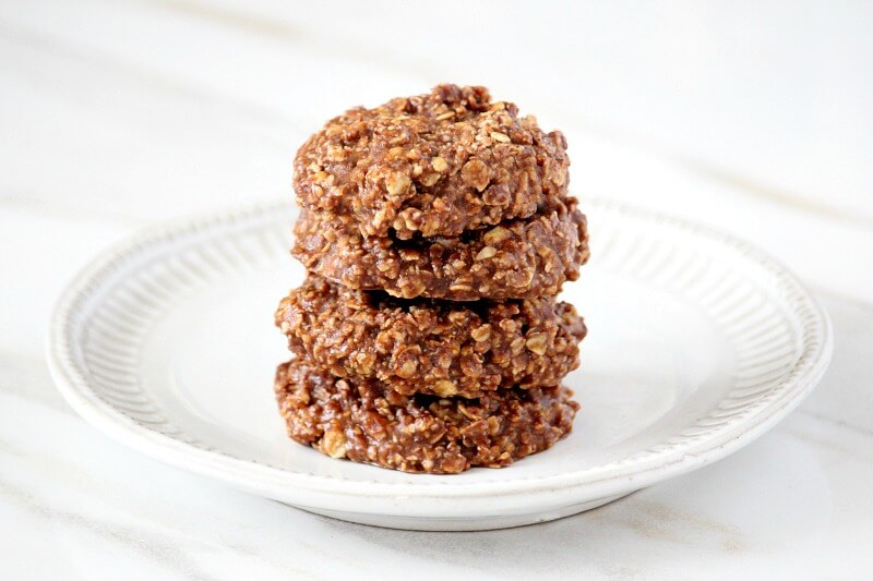 Frontal view of four Gluten-Free Vegan Chocolate Peanut Butter Oatmeal No-Bake Cookies on a white plate and clean white background