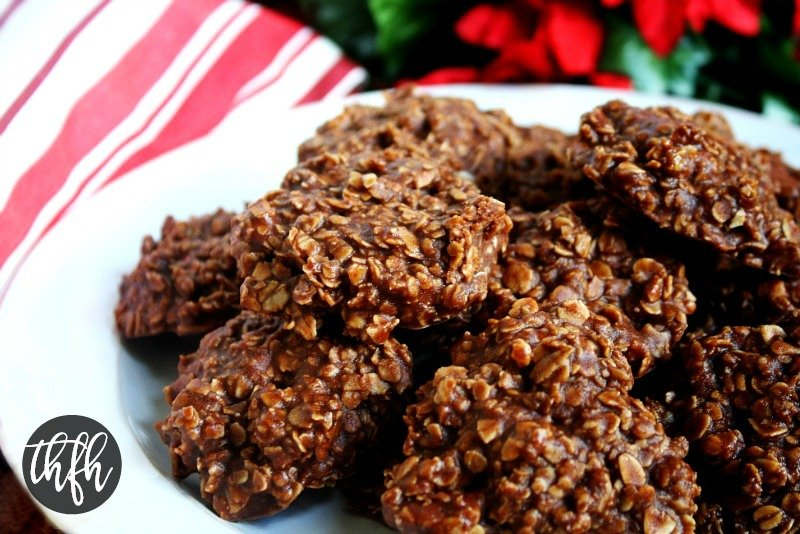 Close up view of Healthy Gluten-Free Vegan Chocolate Peanut Butter Oatmeal No-Bake Cookies on a white plate with Christmas decorations in the background