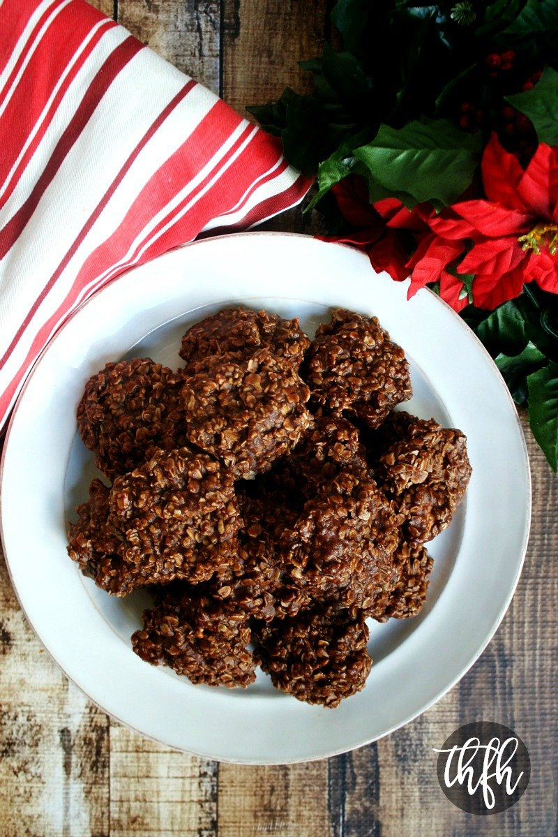 Overhead view of Healthy Gluten-Free Vegan Chocolate Peanut Butter Oatmeal No-Bake Cookies on a white plate on top of a wooden surface with Christmas decorations in the background