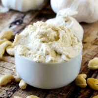 Horizontal image of a small white dip bowl filled with Gluten-Free Vegan Garlic Cashew Spread on a weathered wooden surface with scattered cashews around it
