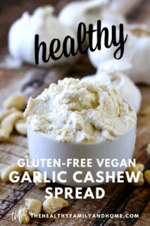 White bowl filled with Gluten-Free Vegan Garlic Cashew Spread with garlic bulbs in the background and text overlay
