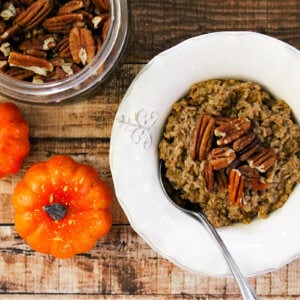 Overhead image of a white bowl of oatmeal next to two small pumpkins on a weathered wood surface