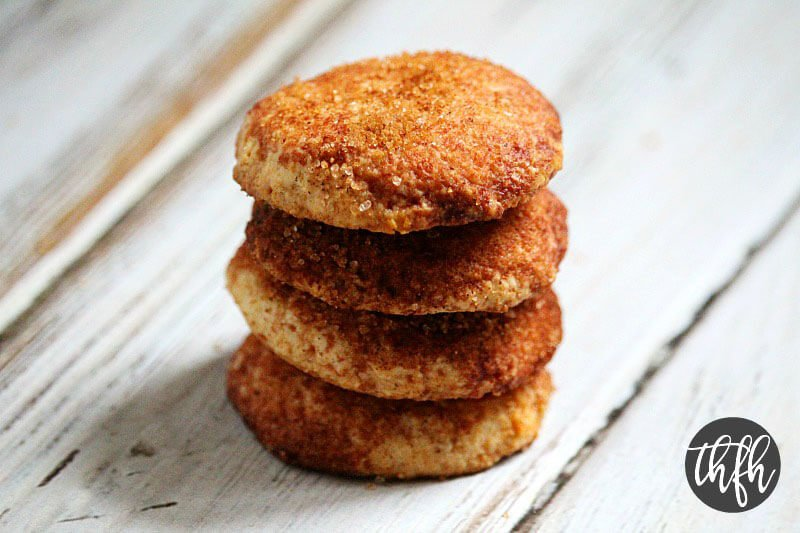 Four Gluten-Free Vegan Flourless Vegan Snickerdoodle Cookies stacked on a white wooden surface
