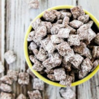 "Overhead image of The BEST Gluten-Free Vegan ""Puppy Chow"" Muddy Buddies in a yellow rimmed bowl on a weathered wooden surface"
