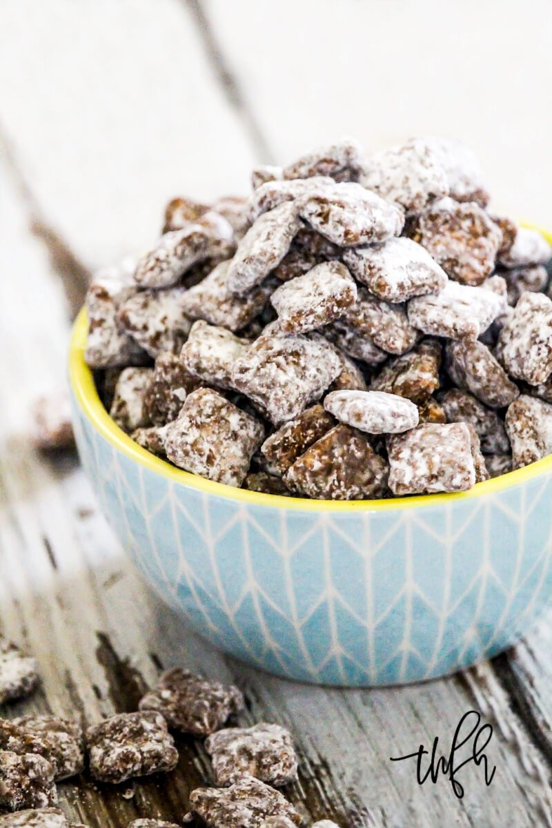 "A blue decorative yellow rimmed bowl filled and overflowing with The BEST Gluten-Free Vegan ""Puppy Chow"" Muddy Buddies on a weathered wooden surface"
