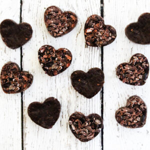 Overhead image of multiple chocolate hearts scattered over a white weathered surface