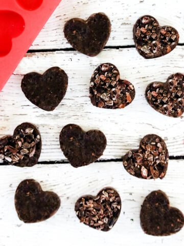 Square overhead image of multiple chocolate fudge hearts scattered on a white weathered wooden surface next to a red silicone heart mold