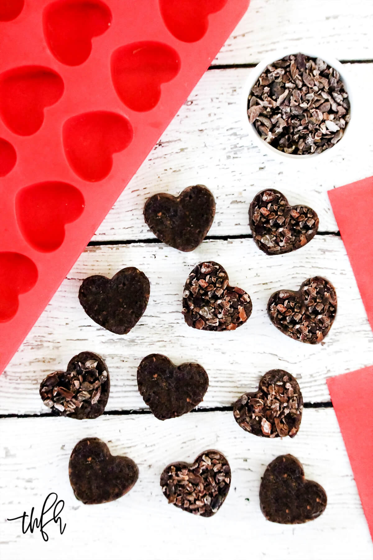 Overhead image of multiple chocolate fudge hearts scattered on a white weathered wooden surface next to a red silicone heart mold
