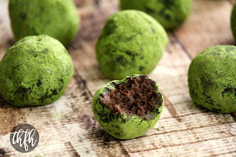 Close-up image of a Matcha Chocolate Avocado Truffle with a bite taken out of it surrounded by more truffles on a weathered wooden surface